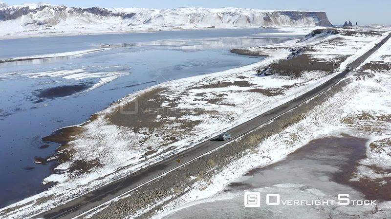 Cars Driving Along a Snowy Road With a Lake Surrounding