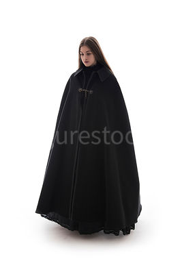 A woman in a big cloak walking towards camera – shot from eye level.