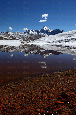 Mt Huayna Potosi reflected in Laguna Milluni after fresh snowfall , Cordillera Real, Bolivia