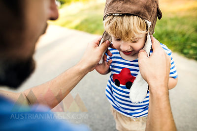 Father putting on pilot hat for his little son