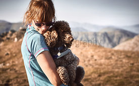 A female hiker cuddling their pet dog at sunset on a mountain summit In the English Lake District, UK.