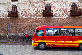 Public bus arriving at bus stop in front of Inca stone wall, Plaza San Pedro , Cusco , Peru