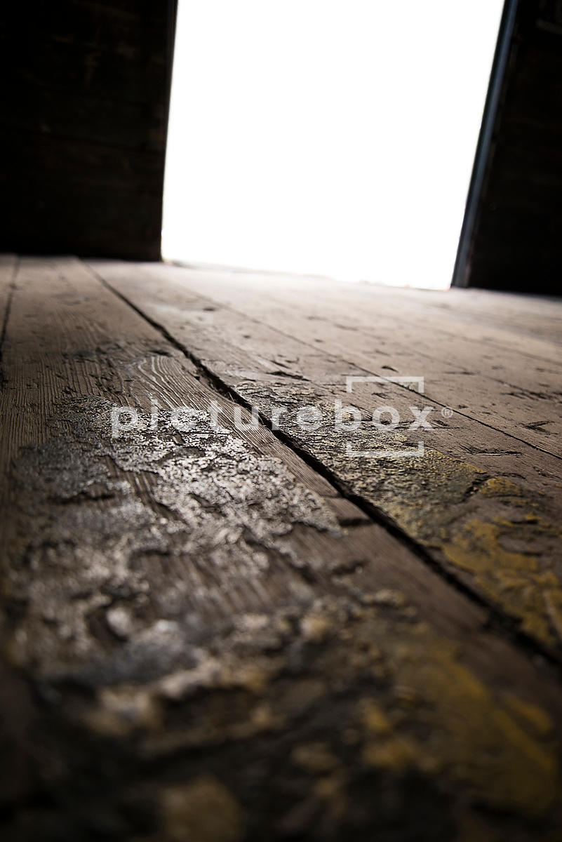 A big blurred open door to an old warehouse, with a focal point on the floor in the foreground, awaiting an object to be added.