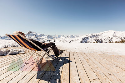 Austria, Damuels, senior man relaxing in deckchair on sun deck in winter landscape