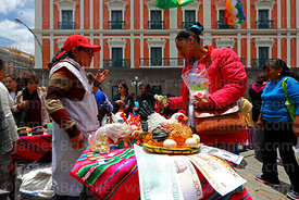Woman buying a miniature ceramic chicken at stall in front of the Presidential Palace, Alasitas festival, La Paz, Bolivia