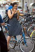 Italy - Verona - A woman eats ice cream whilst sitting on her bicycle