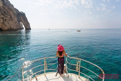 Woman on prow of sailboat in the blue sea of Zakynthos, Greece