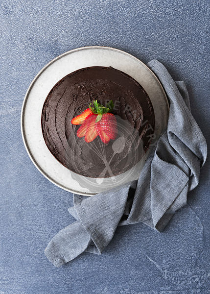 Chocolate dessert cake with chocolate icing and a sliced strawberry on top.