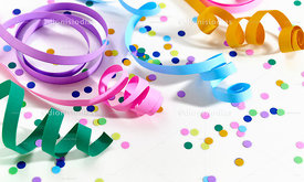 Colorful serpentines in closeup on a white background with confetti