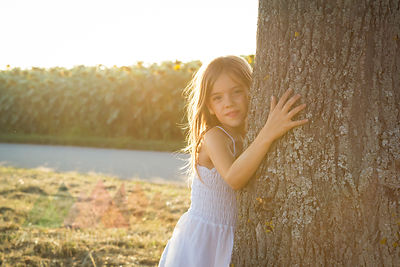 Girl leaning on tree trunk at summer evening