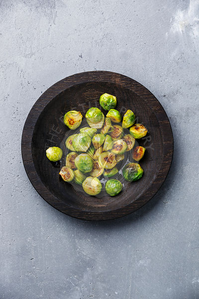 fried Brussels sprouts in wooden bowl on concrete background