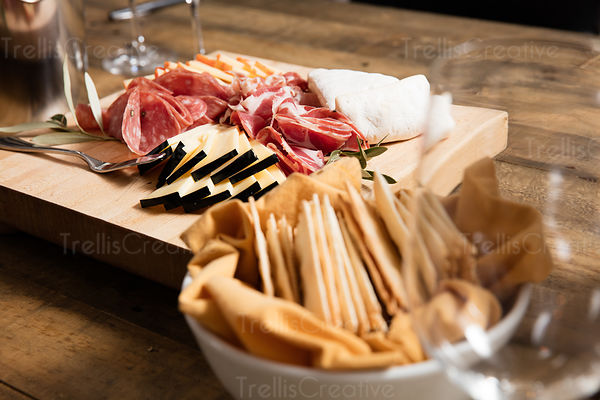 Close-up of crackers and a cheeseboard with cured meats and cheeses