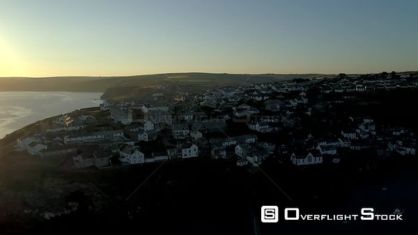 Drone rises past the clifftop houses of Port Isaac to reveal beautiful Cornish coast