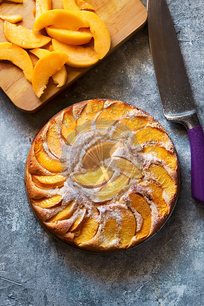 Freshly baked fresh peach cake on a plate.Top view