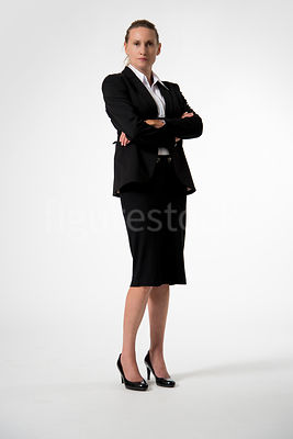 Smartly dressed woman with her arms crossed – shot from mid level.