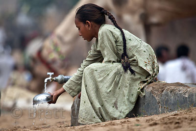 A girl gets water from a communal water spigot in Pushkar, Rajasthan, India
