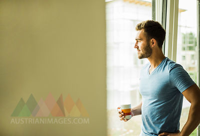 Young man holding coffee cup looking out of window