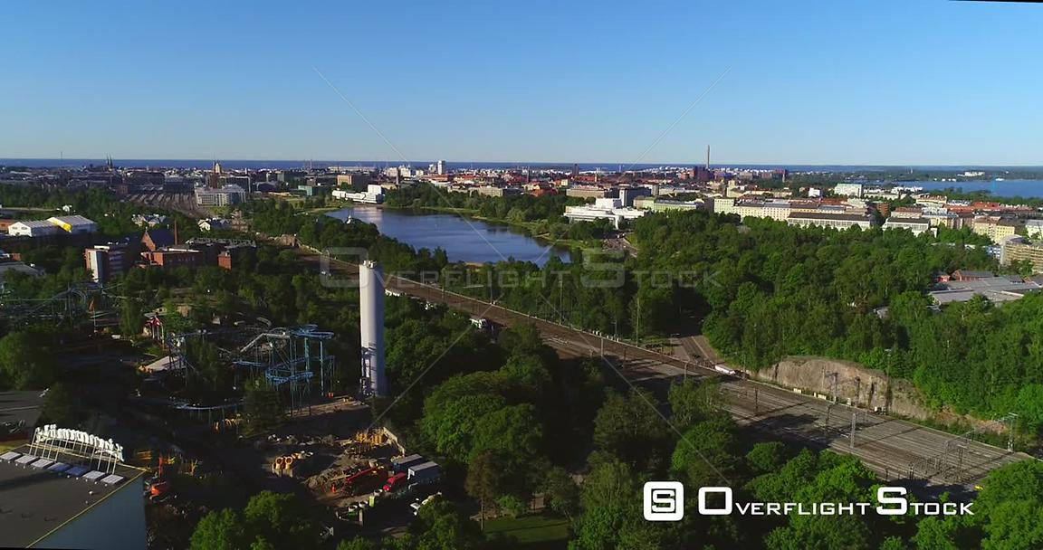Train in a City, Aerial Tracking View of a Train Leaving the Railway Station and Bypassing Linnanmaki, in Helsinki, on a Sunn...