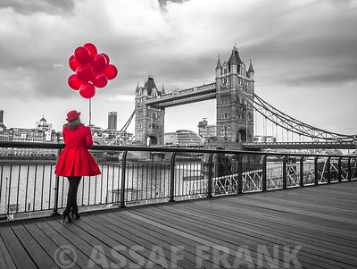 Woman with red balloons, standing on promenade near Tower Bridge, London, UK