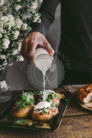 Man's hand pouring sour cream on baked stuffed potatoes with cheese, vegetables and rucola on wooden table. Rustic background