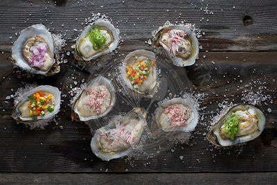 raw oysters on the half shell topped with an assortment of different colorful sauces, sitting on a rustic wood table