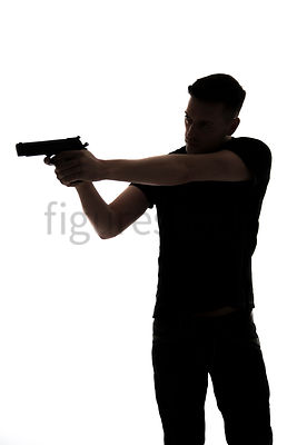 A Figurestock image of a man, in silhouette, pointing a gun – shot from eye level.