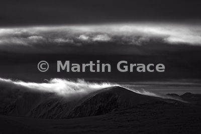 B&W image of late afternoon sun just catching cloud as it pours over the summit of Carn Eilrig, Cairngorm Mountains, Scotland