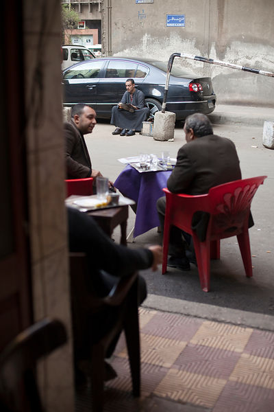 Egypt - Cairo - Men sit outside the Telegraph Cafe while a shoe shone works, off Halim Square,
