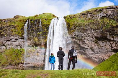 Family standing in front of Seljalandsfoss waterfall, Iceland