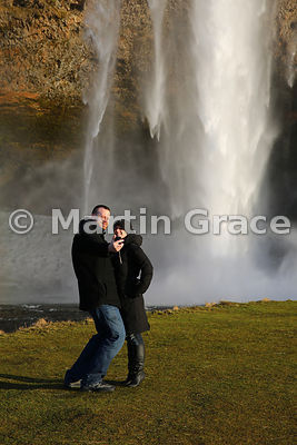 The Selfie - a young couple photographing themselves on a mobile phone in front of Seljalandsfoss waterfall