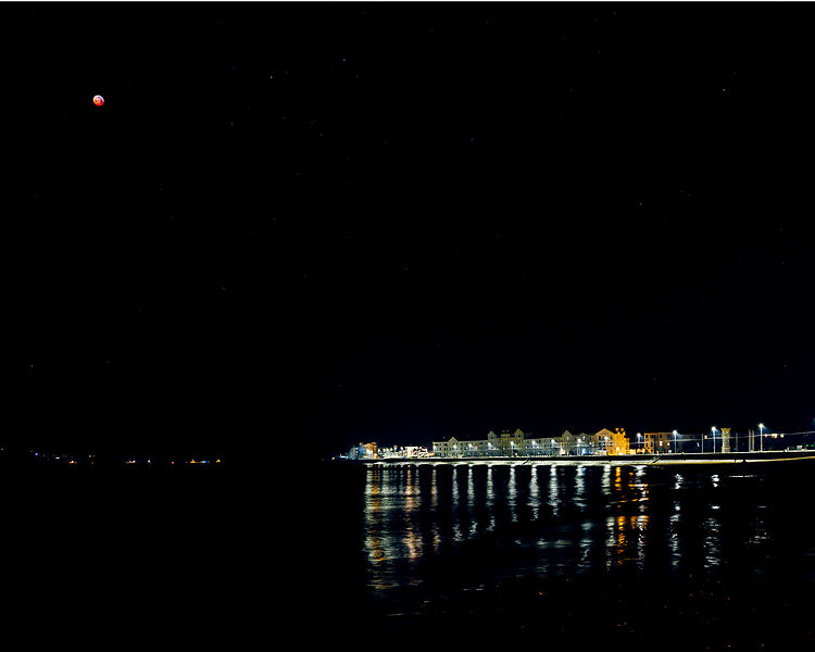 Blood red moon during Lunar Eclipse over sea front at Exmouth, Devon, UK