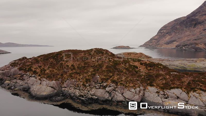 Aerial drone shot over a small island revealing the sea on Isle of Skye, Scotland
