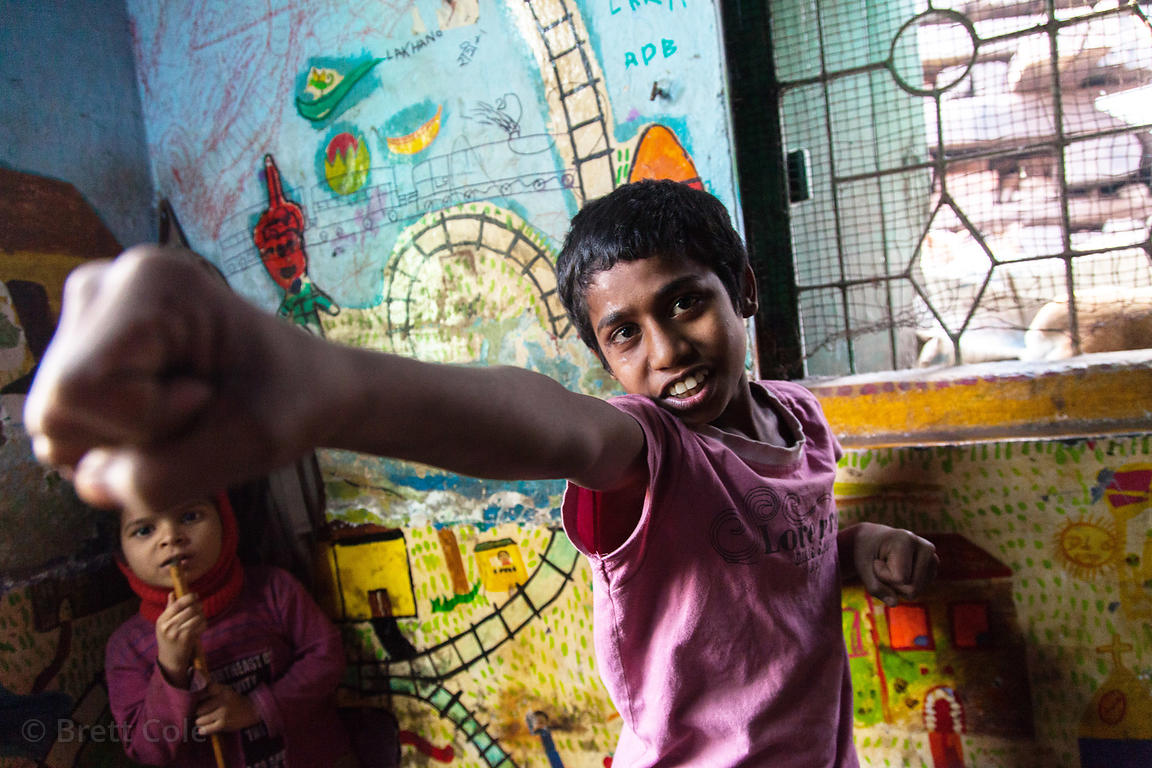 A boy practices karate at a shelter for homeless or otherwise at-risk boys at Sealdah Station, Kolkata, India