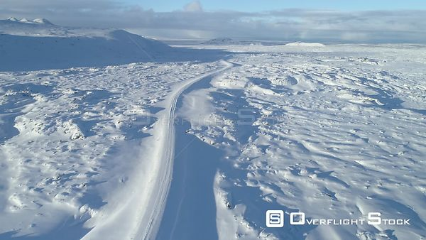 Aerial Revealing Shot of Winding Snow Covered Mountain Road Lava Field Iceland Day