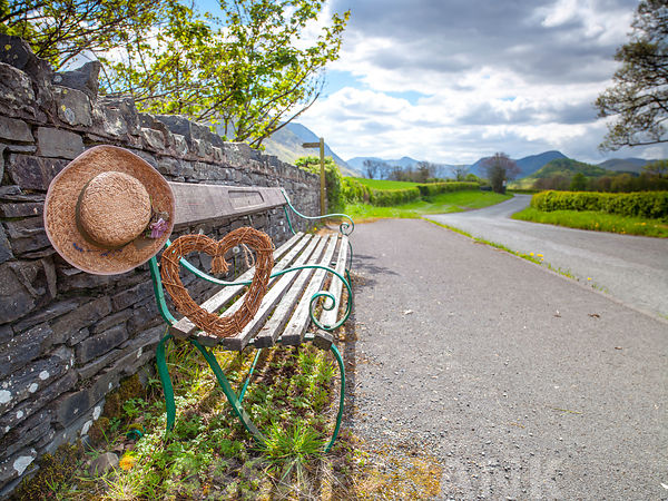 Bench with a hat and heart on countryside road