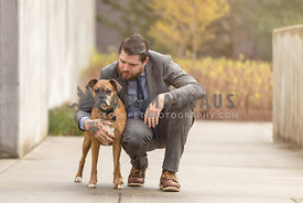 man in suit hugging boxer dog