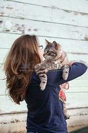 blue-eyed tabby cat being held over the shoulder by female owner