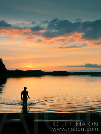 Woman in lake at sunset