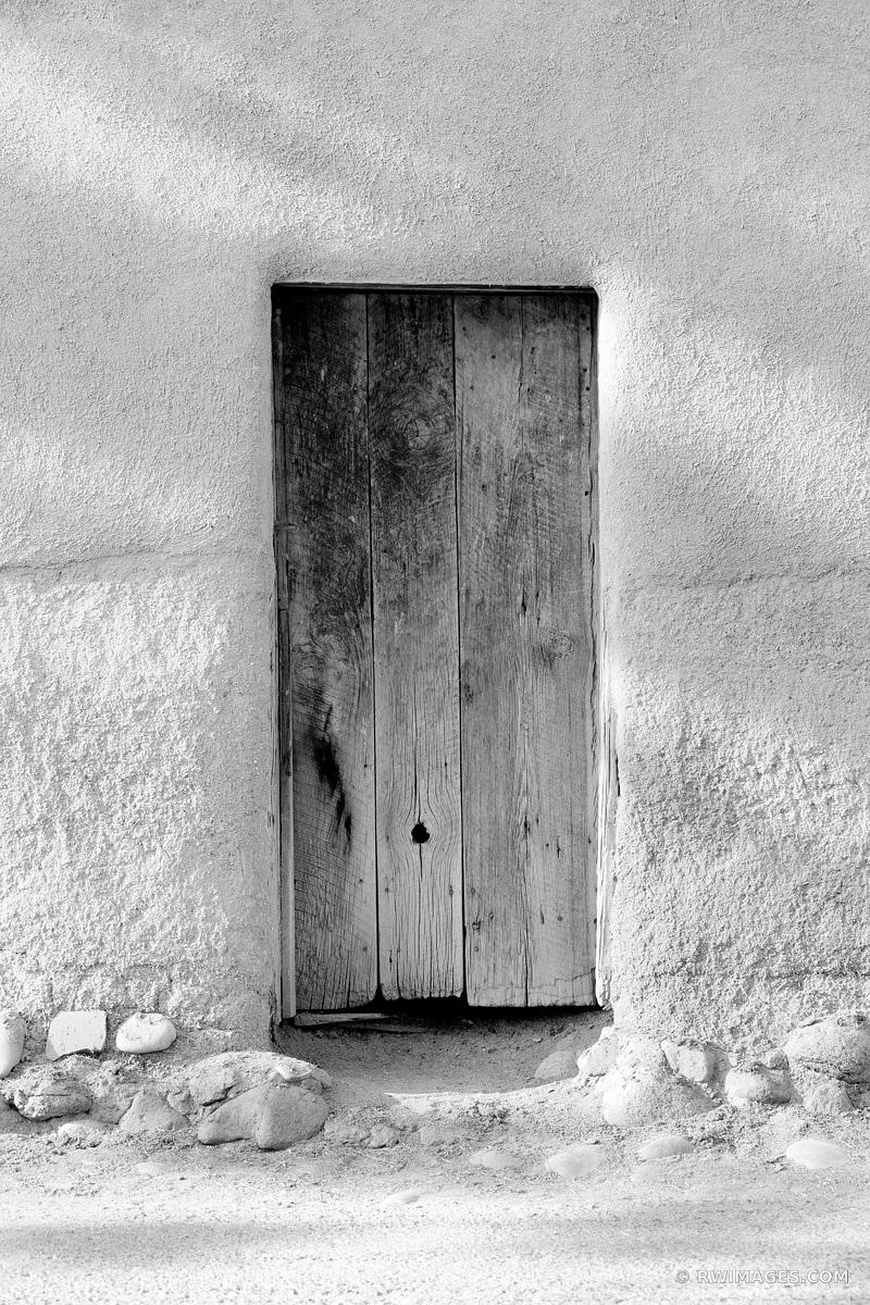 OLD WOODEN DOOR OLDEST HOUSE ADOBE BUILDING WALL SANTA FE NEW MEXICO BLACK AND WHITE VERTICAL