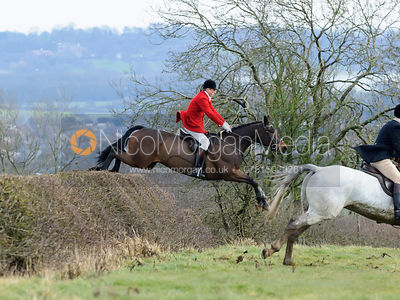 Nicholas Leeming jumping a hedge above Wilson's covert