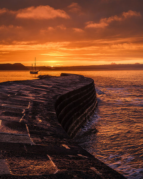 Colourful sunrise with Irene anchored off The Cobb in Lyme Regis, Dorset, UK