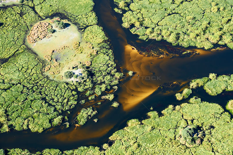 Aerial view of the Okavango delta,  with a meandering channel with a sandy bed forms a lagoon in the swamp with islands, Bots...
