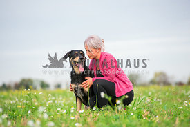 Woman cuddling with her black dog in flower field
