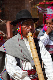 Musician playing wooden flutes or pinkillus at San Santiago festival , Taquile Island , Peru