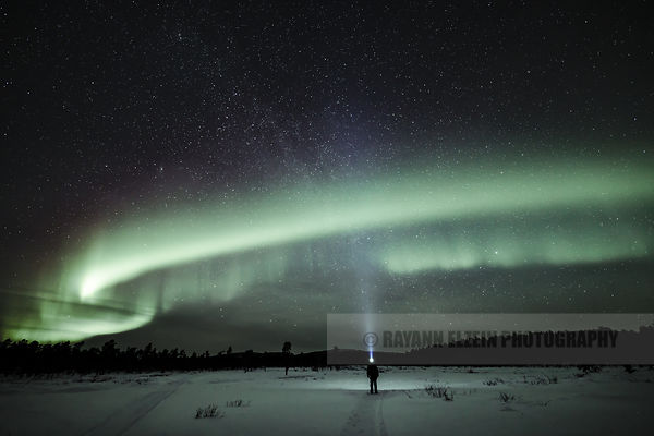 Standing under the northern lights in the north of Lapland, Finland