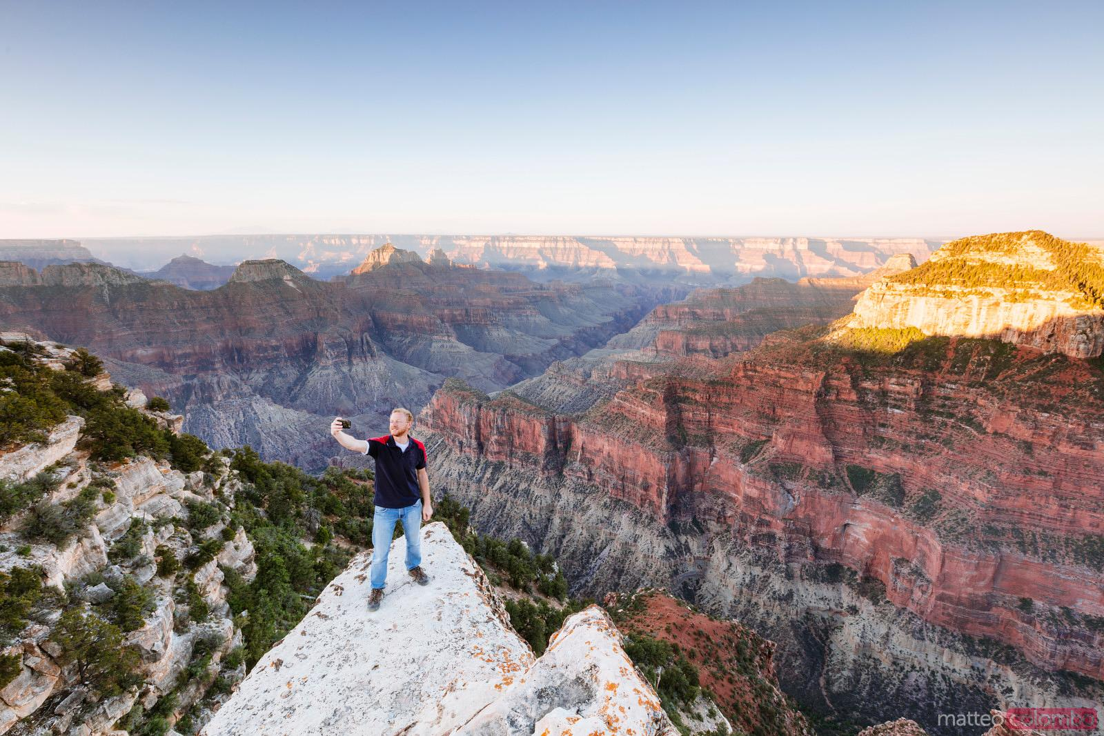 Man taking a selfie on the edge of Grand Canyon, USA