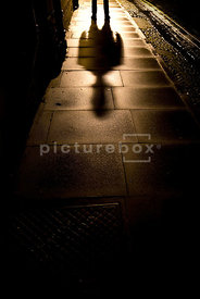 An atmospheric image of the shadow of a mystery man, standing in an empty street at night.
