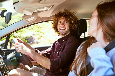 Laughing young man driving car looking at his girlfriend