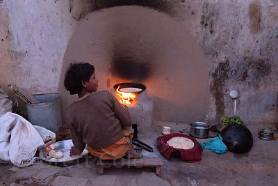 Girl tending an oven in a slum area on Ramnagar Rd., Varanasi, India.