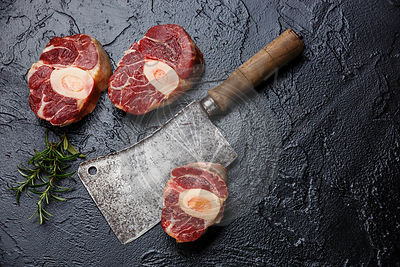Raw fresh cross cut veal shank for making Osso Buco on black background with meat cleaver